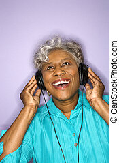 Woman listening to headphones. - Mature adult African...