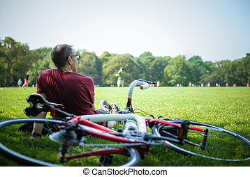 Resting Cyclist - A male cyclist, seats on the grass,...
