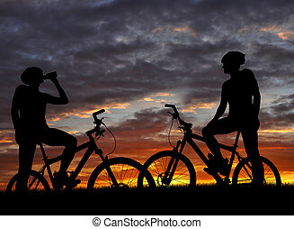 two mountain biker silhouette in sunrise
