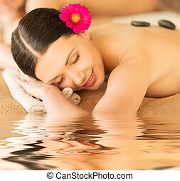 woman in spa with hot stones