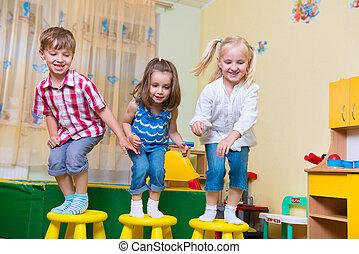 Group of happy preschool kids jumping in kindergarten