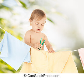 baby doing laundry - bright picture of adorable baby doing...