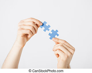 two hands trying to connect puzzle pieces
