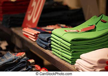 Colour shirts at shelf in shop - Various colour shirts at...