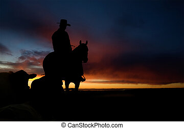 Cowboy Silhouette - A cowboy on a hill against a sunset