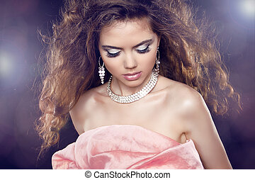 Beauty Glamour Portrait of sexy woman with long curly hair and fashion makeup over party lights.