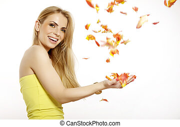 Beautiful and attractive smiling blonde young adult girl with the bouquet of red and yellow tulips flowers isolated on a white background