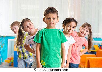 Group of five preschoolers standing in playroom