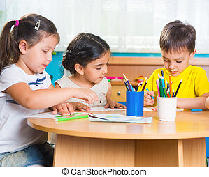Group of cute little preschool kids drawing with colorful...