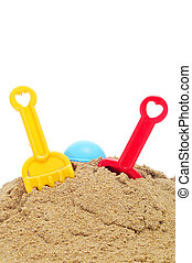 playing in the sand - toy shovels and rakes on the sand, on...