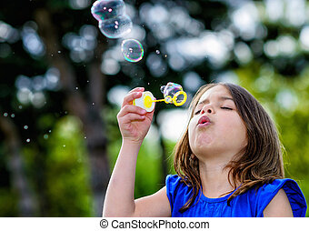 beautiful child blowing bubbles in a meadow with greenery in...