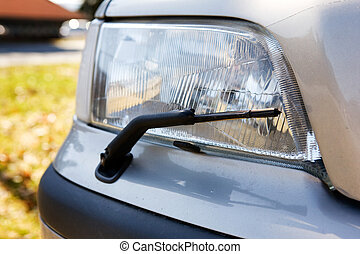 Headlight Detail - A headlight with a wiper detail on a car