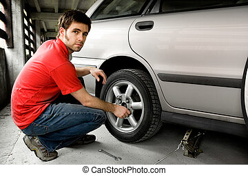 Tire Repair - A male chaning a tire on a car