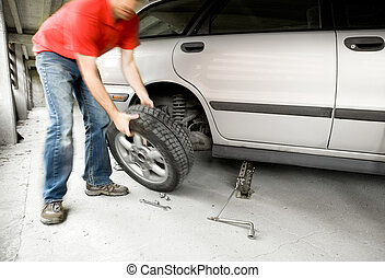 Quick Wheel Change - A male changing a tire on a car in a...