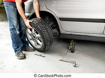 Tire Change - A male changing a tire on a car in a garage