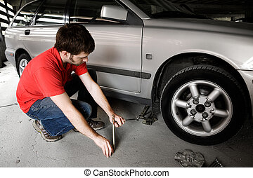Auto Repair - A male jacks up a car in a garage - fixing the...