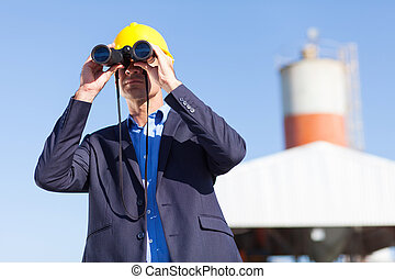 industrial manager with binoculars outdoors