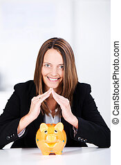 Businesswoman Joining Fingers Above Piggybank At Desk -...