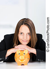 Serious Businesswoman With Piggy Bank At Desk - Portrait of...