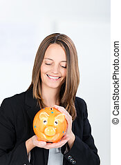 Businesswoman Holding Piggy Bank In Office - Portrait of...