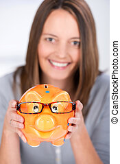 Businesswoman Holding Piggy Bank With Glasses In Office -...