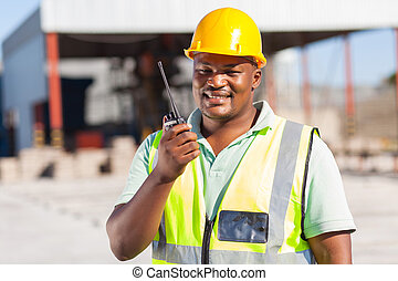 builder talking on radio - african male builder talking on...