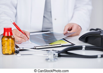 Doctor Writing Notes While Holding Xray At Desk - Midsection...