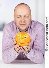 Businessman Holding Piggybank In Office - Portrait of mature...