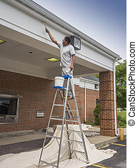 House painter - Hispanic male painting building soffit