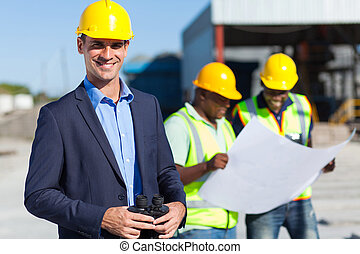 construction supervisor with binoculars - smiling caucasian...