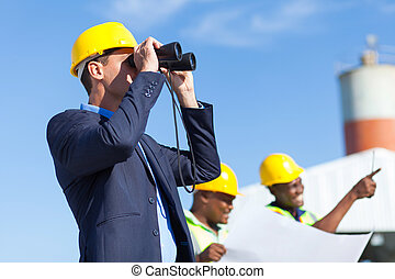 architect using binoculars looking at construction site with...