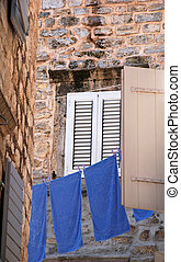 Old wall, window and blue linen Italy - Old stone wall,...