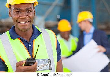 african american industrial worker with walkie talkie