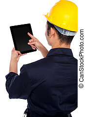 Back pose of worker operating tablet device - Young...