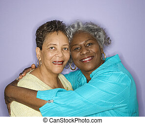 Women smiling and embracing. - Mature adult African American...