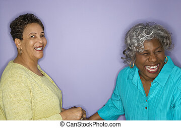 Women laughing - Mature adult African American females...