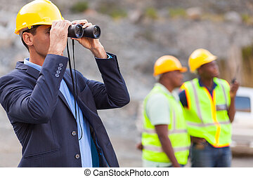 mine manager with binoculars