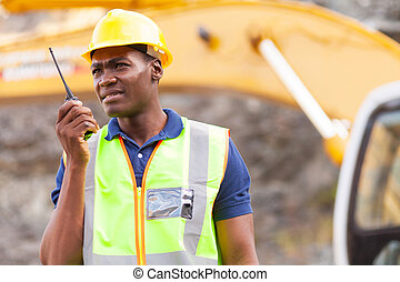 african american mine worker with walkie-talkie at mining...