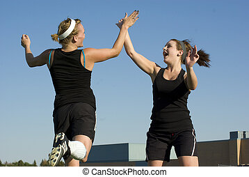 Soccer Girls celebrate with a high five - Playing soccer...