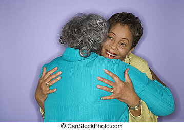 Women embracing. - Mature adult African American females...