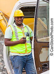 african road construction worker on bulldozer and holding a...
