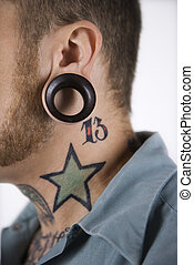 Man with tattoos and piercings. - Caucasian mid-adult man...