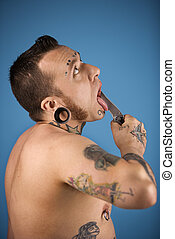Man holding knife to tongue. - Caucasian mid-adult man with...