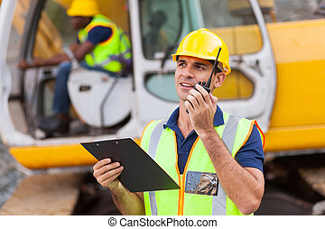 construction foreman talking on walkie-talkie holding...
