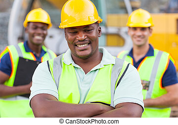 african construction worker with colleagues - smiling...