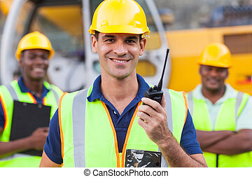 contractor with walkie-talkie - portrait of smiling...