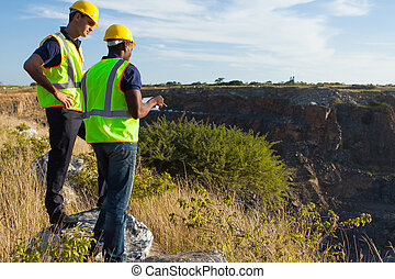 surveyors working at mining site - two male surveyors...