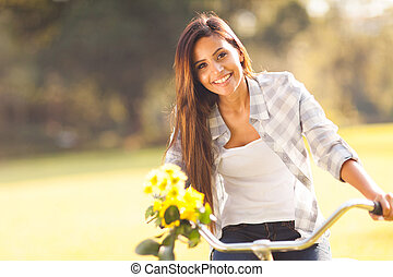 woman with flowers riding a bicycle - beautiful woman with...