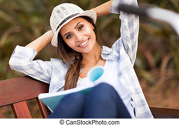 pretty college student reading book at the park - cheerful...