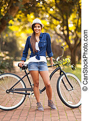 young woman posing next to bike